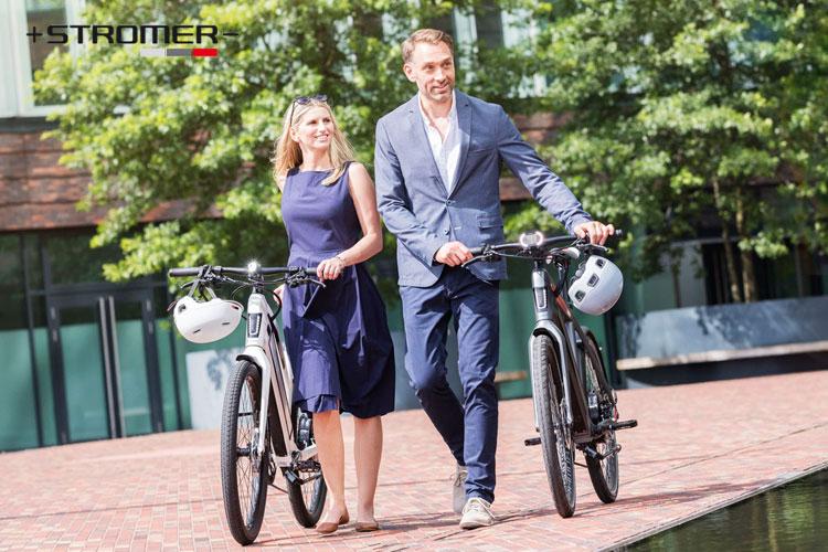 Ciclisti di città portano a mano le loro ebike Stromer