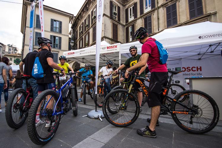 Ciclisti in sella a bici elettriche per le strade di Lecco